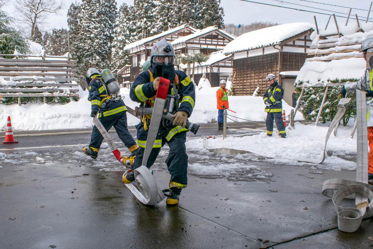 消防隊員、ホースを伸ばす